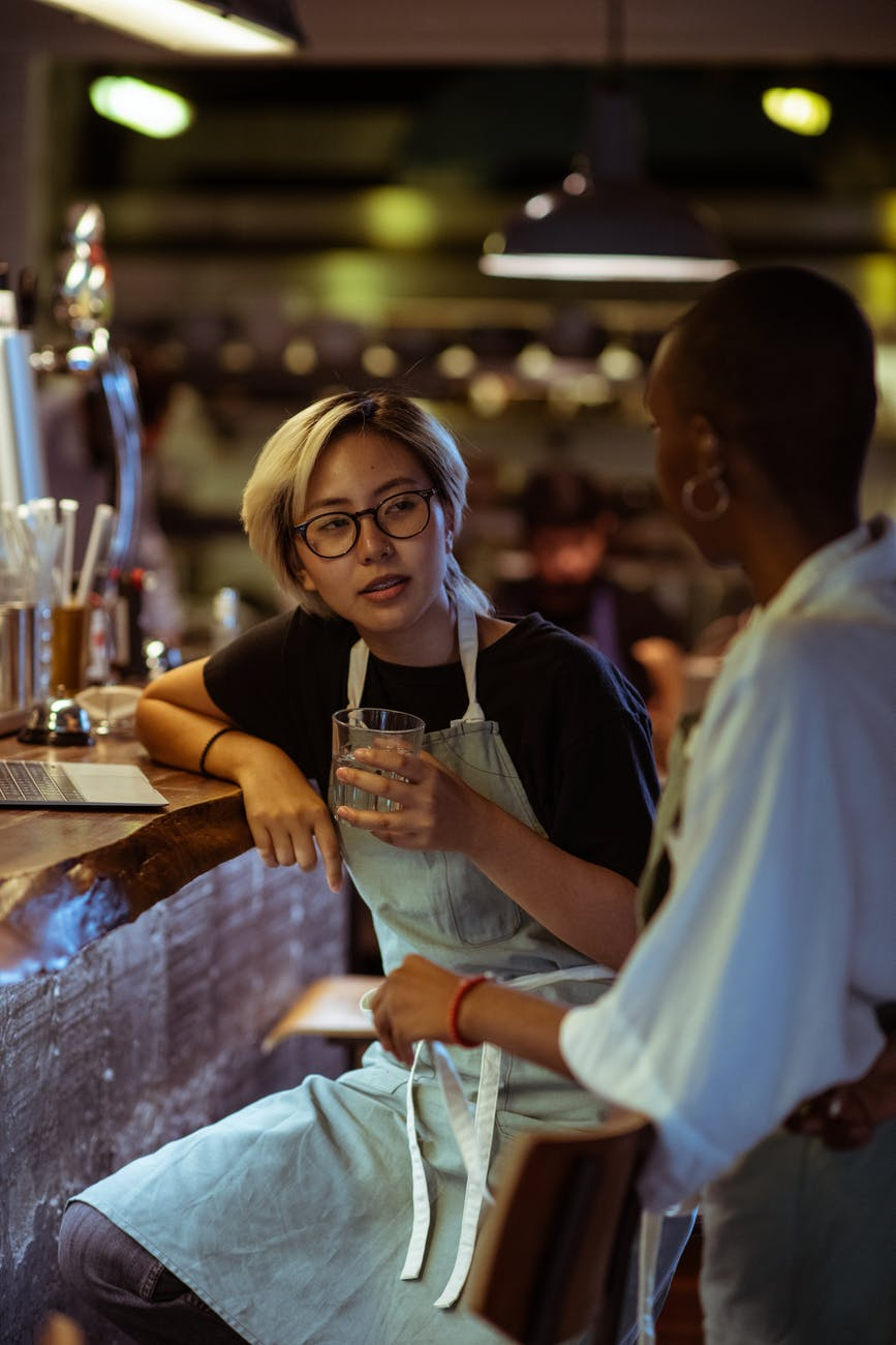 bar workers in aprons chatting near bar counter